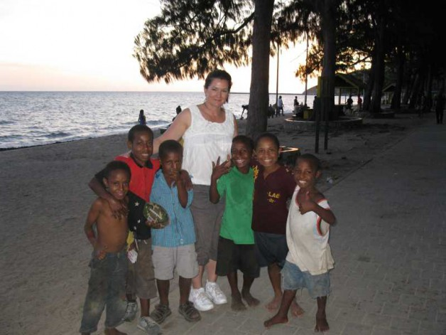 Professor Taylor with local children on a beach in Port Moresby
